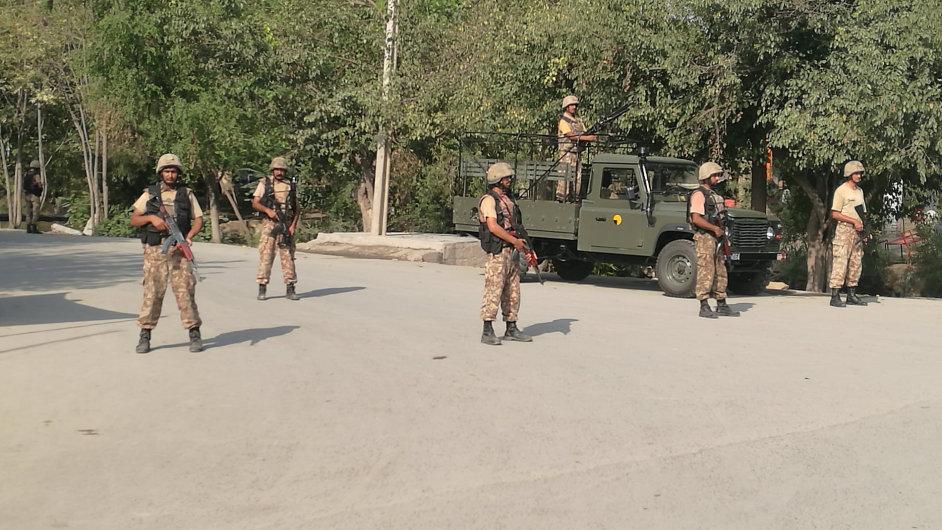 Vojáci hlídají cestu u křesťanské osady, kterou předtím napadli teroristé.