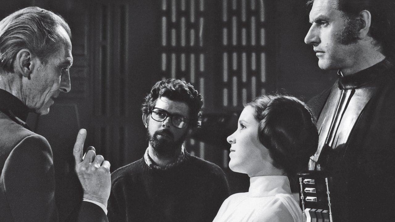 Na snímku z natáčení čtvrté, v pořadí ovšem první epizody Hvězdných válek je uprostřed režisér George Lucas.