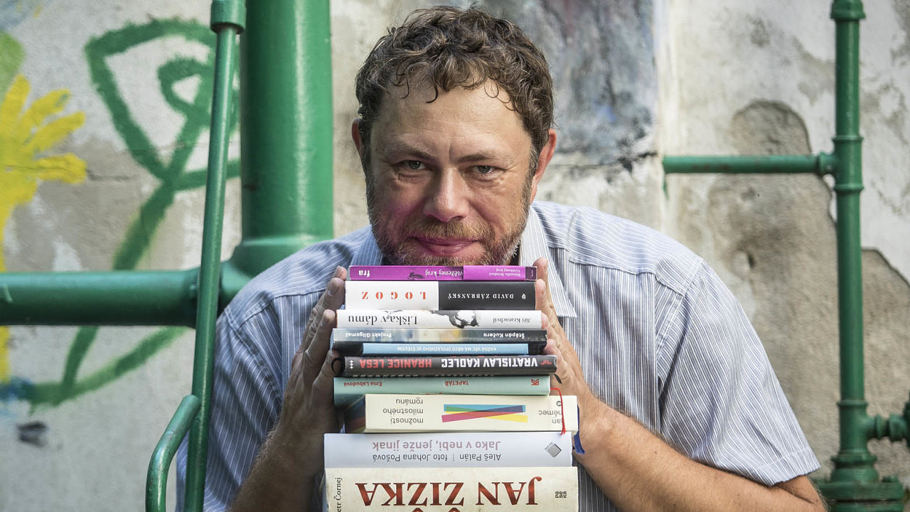 Pavel Mandys chová na klíně některé z 26 knih nominovaných na Magnesii Literu za loňský rok.