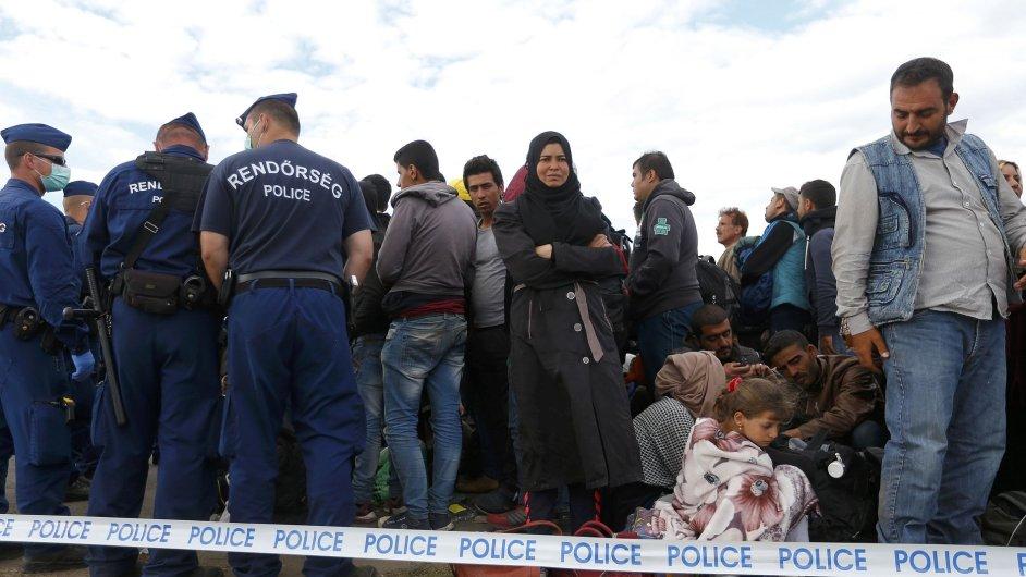 Maďarská policie hlídá uprchlíky čekající na autobus ve sběrném táboře v Roszke.