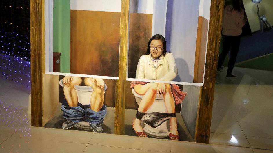 Návštěvnice pózuje v instalaci, která pracuje s optickým klamem, na výstavě v Pekingu.