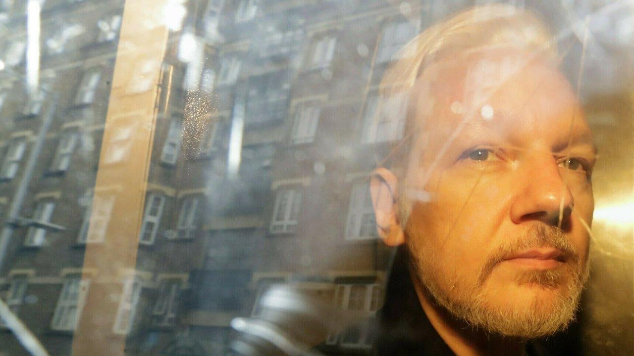 Buildings are reflected in the window as WikiLeaks founder Julian Assange is taken from court