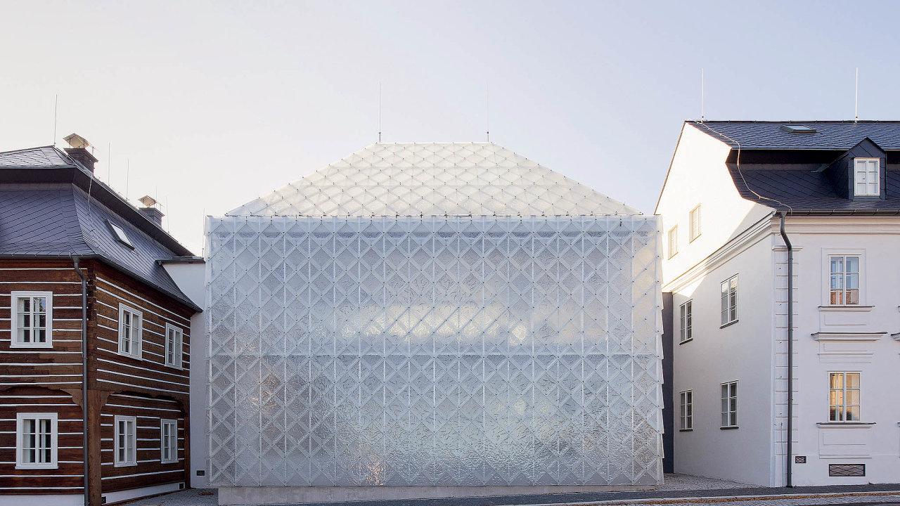 Nový dům objemem isiluetou navazuje nastarší sousedy, současnost architekti vyjádřili fasádou připomínající skleněný závoj.