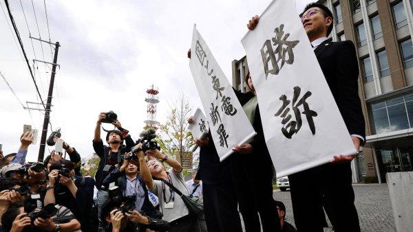 """Právníci vítězné žaloby s transparenty s nápisem """"Vítězství"""" poté, co okresní soud ve Fukušimě rozhodl ve prospěch poškozených."""