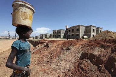 Z afrických zemí dluží Číně nejvíce peněz Angola (na snímku pořízeném v hlavním městě provincie Huila Lubangu prochází žena kolem stavby placené Číňany).