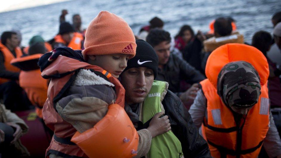 Muž drží dítě, zatímco se vyloďují na pobřeží řeckého ostrova Lesbos.