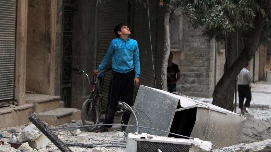 Mladík se dívá na poškozené domy po náletu v Aleppu.