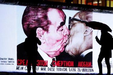 Pouliční umění. Fotografie bratrského polibku mezi vůdcem sovětské totality Leonidem Iljičem Brežněvem adlouholetým šéfem režimu NDR Erichem Honeckerem zroku 1979 jako street art na zbytcích zdi.