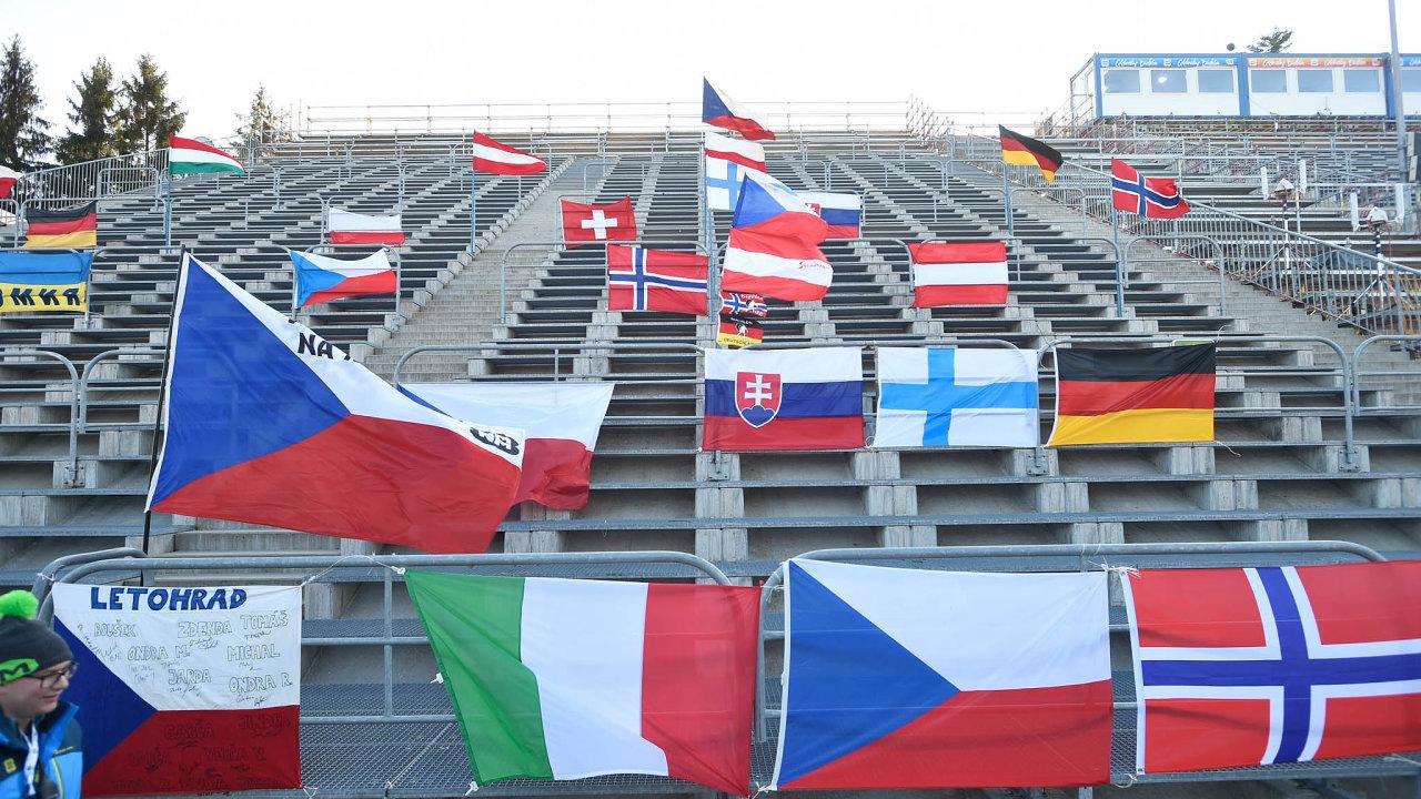 Lidé z organizačního výboru rozvěsili vlajky na prázdné tribuně biatlonového areálu v Novém Městě na Moravě. Závody Světového poháru v biatlonu se na Vysočině budou konat bez diváků.