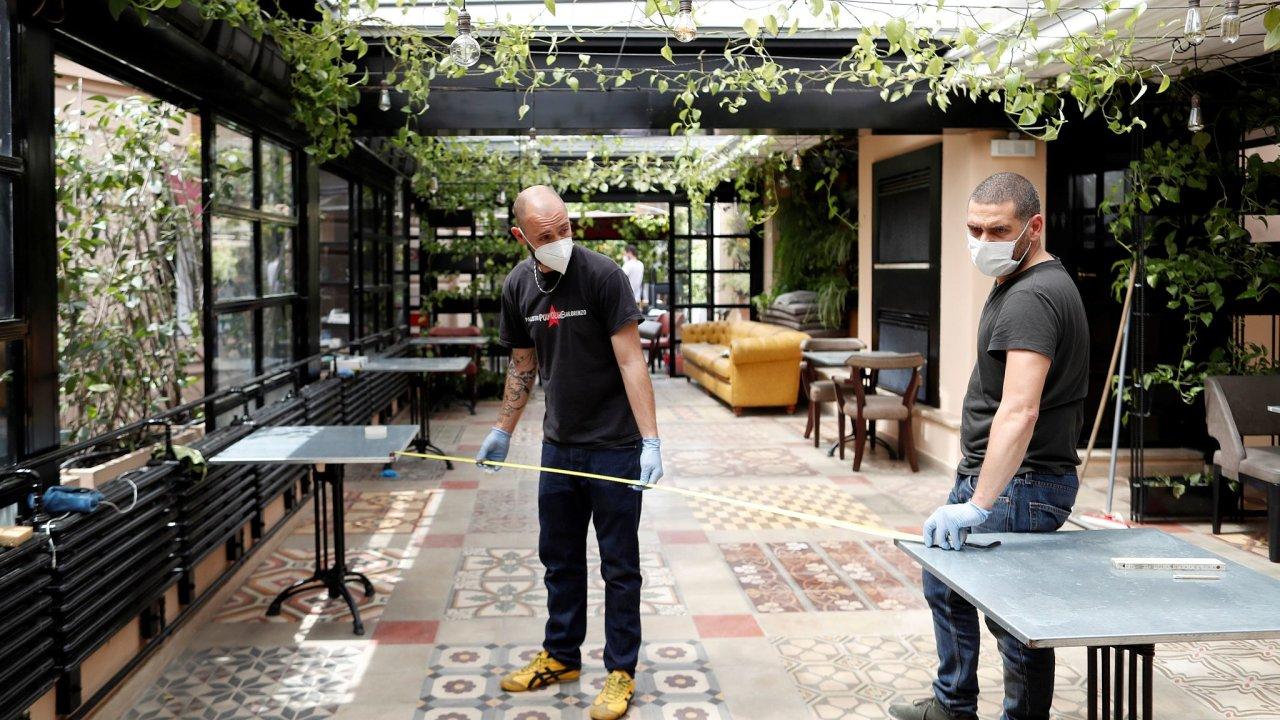 Zaměstnanci michelinské restaurace Marco Martini v Římě připravují restauraci na znovuotevření s dodržování povinných rozestupů.