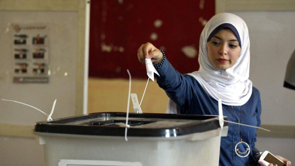Mladá žena vhazuje hlasovací lístek do urny během prezidentských voleb v Egyptě.