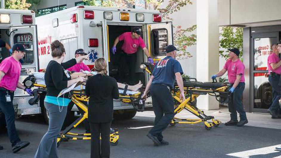Záchranáři odváží zraněného. Na vyšší odborné škole v oregonském Roseburgu střelec zabil devět lidí.