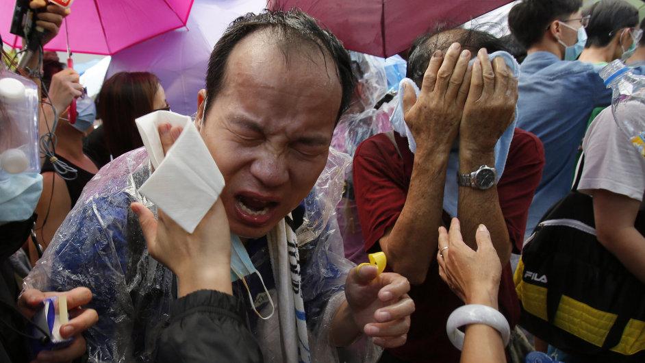 Demonstranti v Hongkongu se schovávají před slzným plynem.