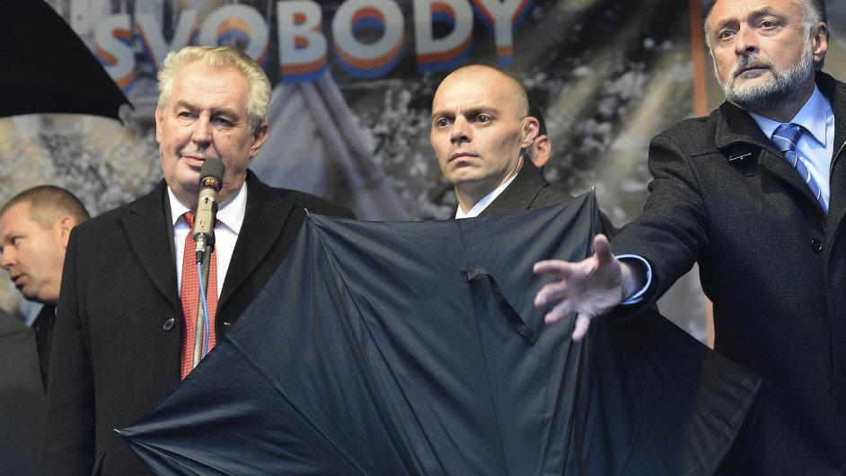 Ochranka pomocí deštníků chránila Miloše Zemana.