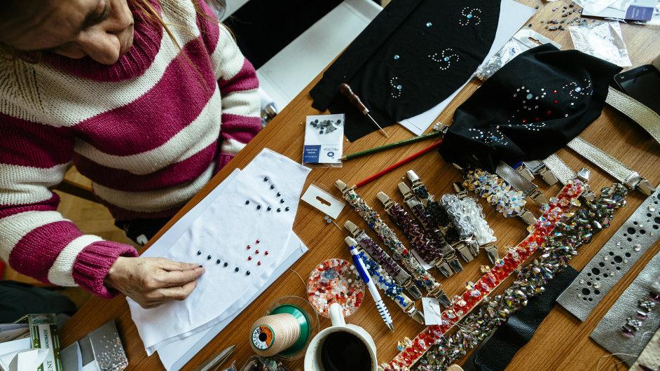 Bezdomovkyně vyrábí šperky.