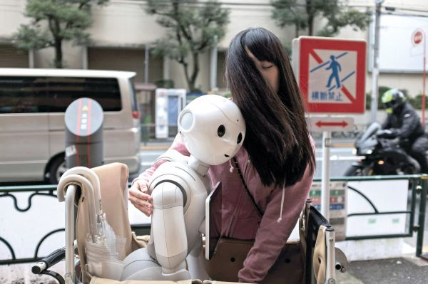Tomomi Ota pushes a cart loaded with her humanoid robot Pepper in Sunday afternoon for her weekly walk with Pepper in Tokyo in Tokyo