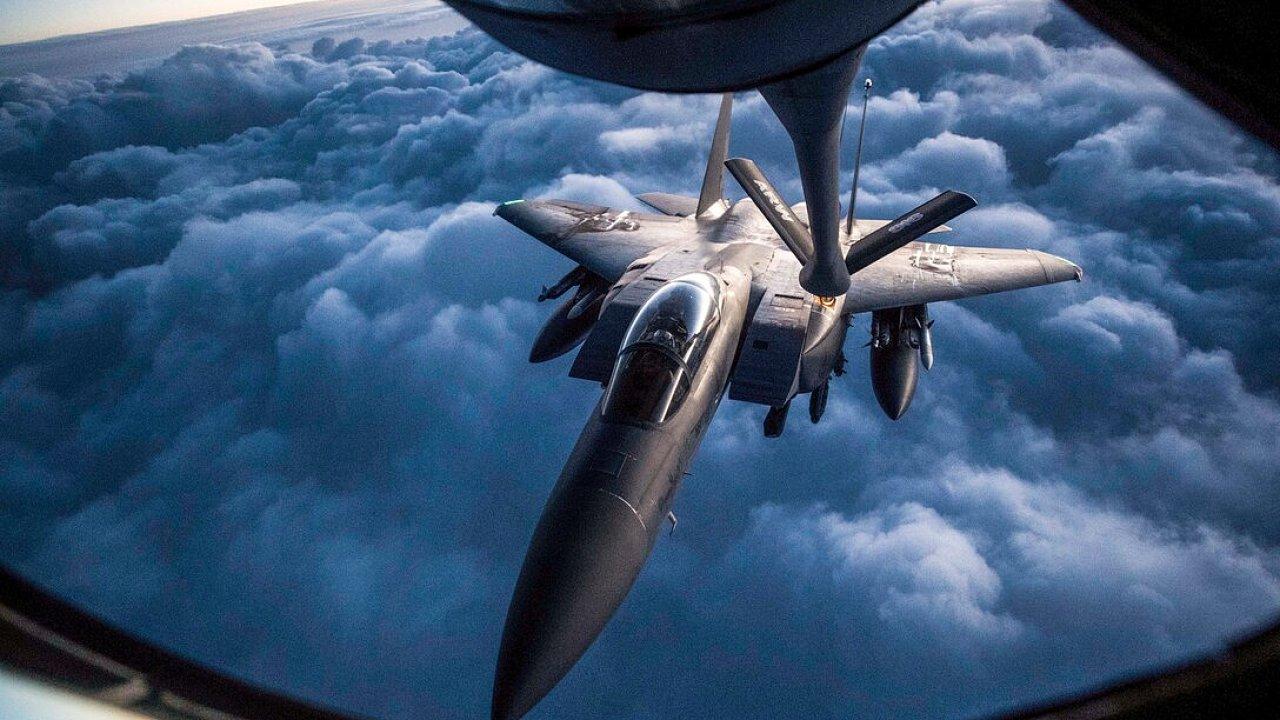Americký bitevník F-15 tankuje za letu z leteckého tankeru KC-135 během operací nad Irákem v roce 2018. Od roku 2010 americká armáda experimentuje se zeleným palivem pro své bojové letouny.