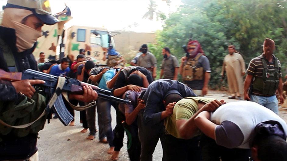 Příslušník ISIS míří zbraní na Iráčany.