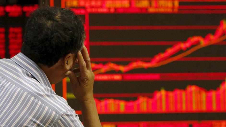 Investor sleduje elektronickou tabuli s informacemi o pohybu cen akcií v Pekingu.