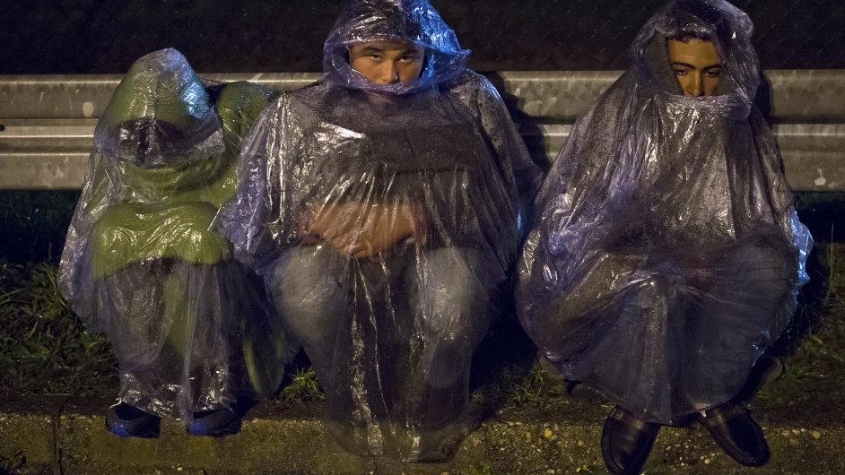 Migranti sedí v dešti, snaží se přejít hranice mezi Chorvatskem a Slovinskem. Slovinsko omezilo příliv běženců na 2500 denně.