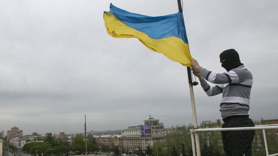 Proruský separatista sundavá ukrajinskou vlajku z doněcké vládní budovy.