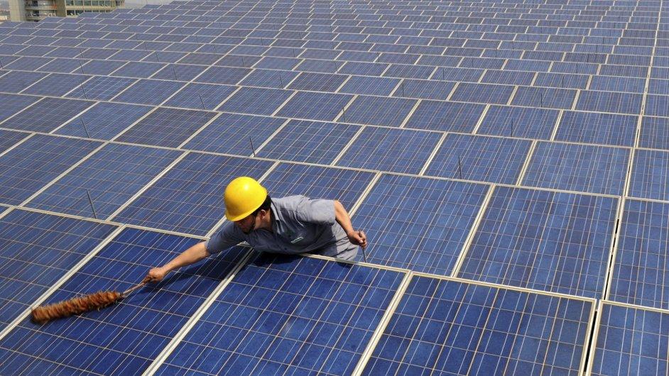 Dělník čistí solární panely na střeše nákupního centra v Číně.