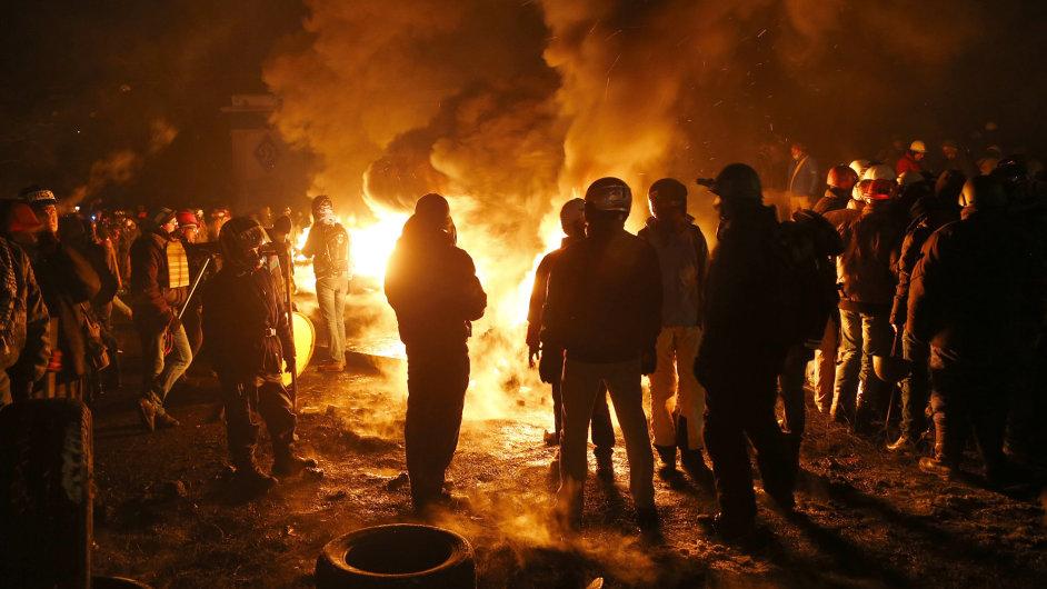 Protestanti v Kyjevě se v pátek ráno zahřívají za barikádami.