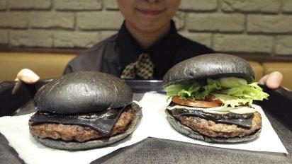 Employee of Burger King Rumi Sekine shows off a Kuro Diamond burger