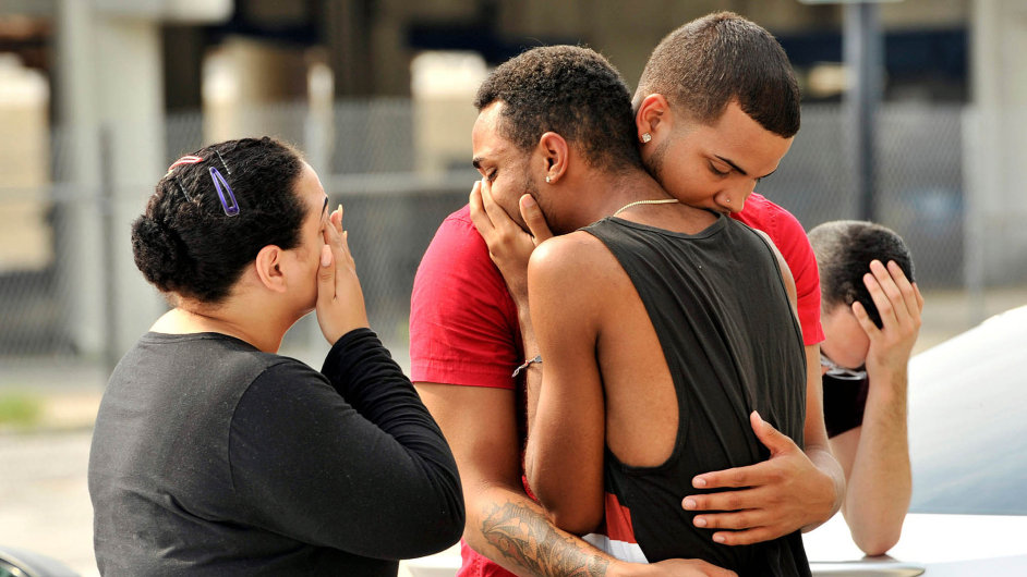 Friends and family members embrace outside the Orlando Police Headquarters during the investigation of a shooting at the Pulse night club