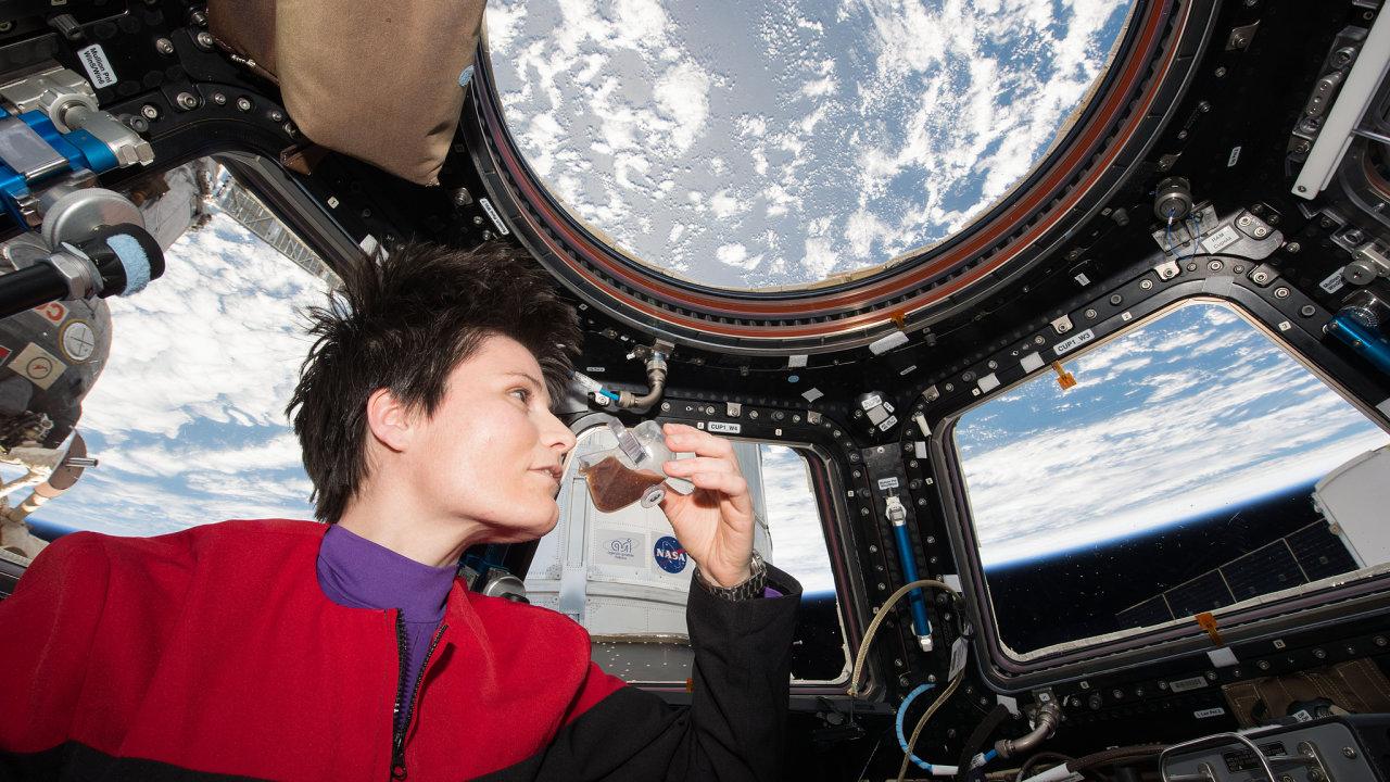 """Astronautka ESA Samantha Cristoforettiová popíjí kávu ze speciálního """"zero-G"""" šálku v pozorovatelské kopuli Mezinárodní vesmírné stanice."""