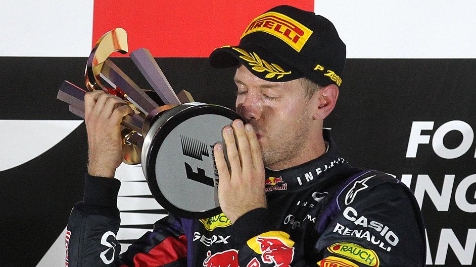 Vítěz Vettel líbá trofej.