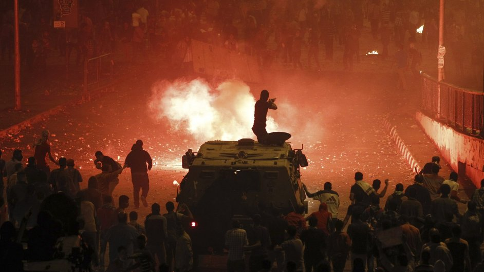 Policista na obrněném voze obklopeném odpůrci exprezidenta Mursího pálí v Káhiře gumovými projektily mezi Mursího stoupence z Muslimského bratrstva