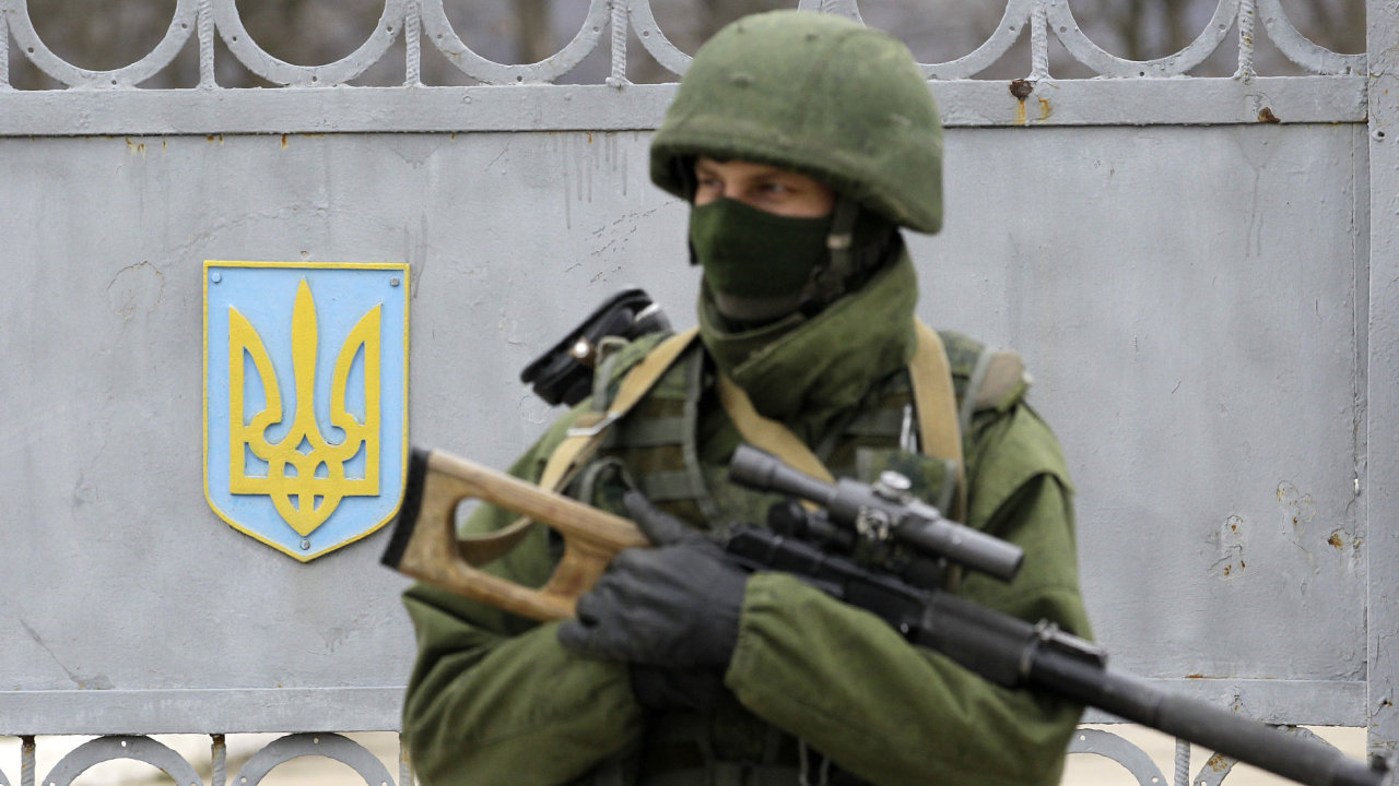 Neoznačený ozbrojenec blokující vchod do ukrajinské vojenské základny