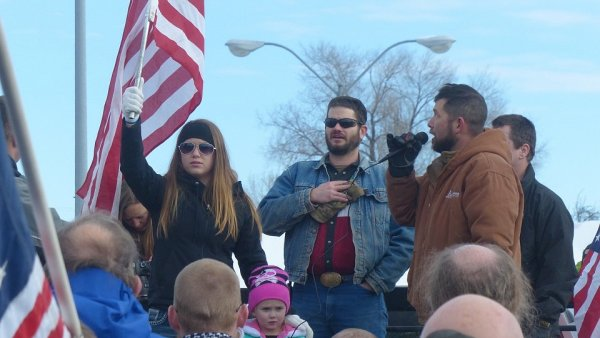 Organizátoři sobotního protestního průvodu zpívají hymnu.