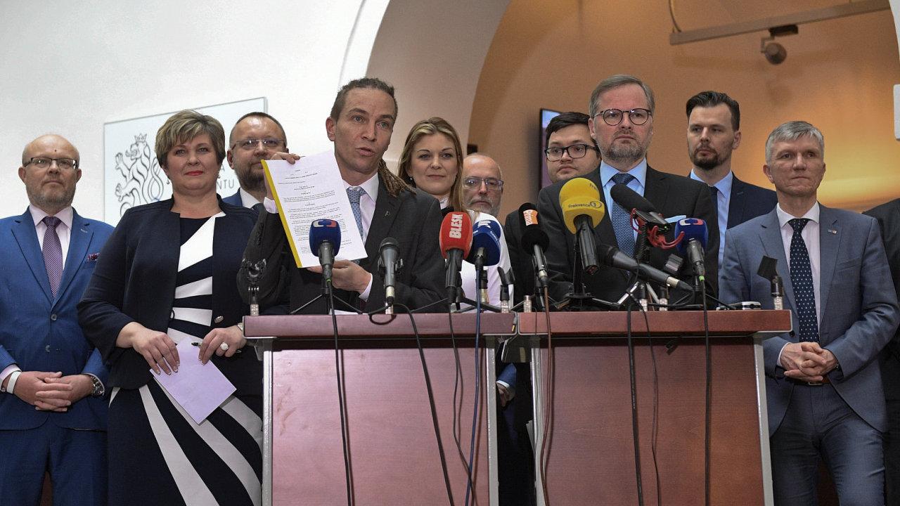 Předseda pirátů Ivan Bartoš (u řečnického pultu vlevo) ukazuje návrh zákona na právo občana na digitální služby.