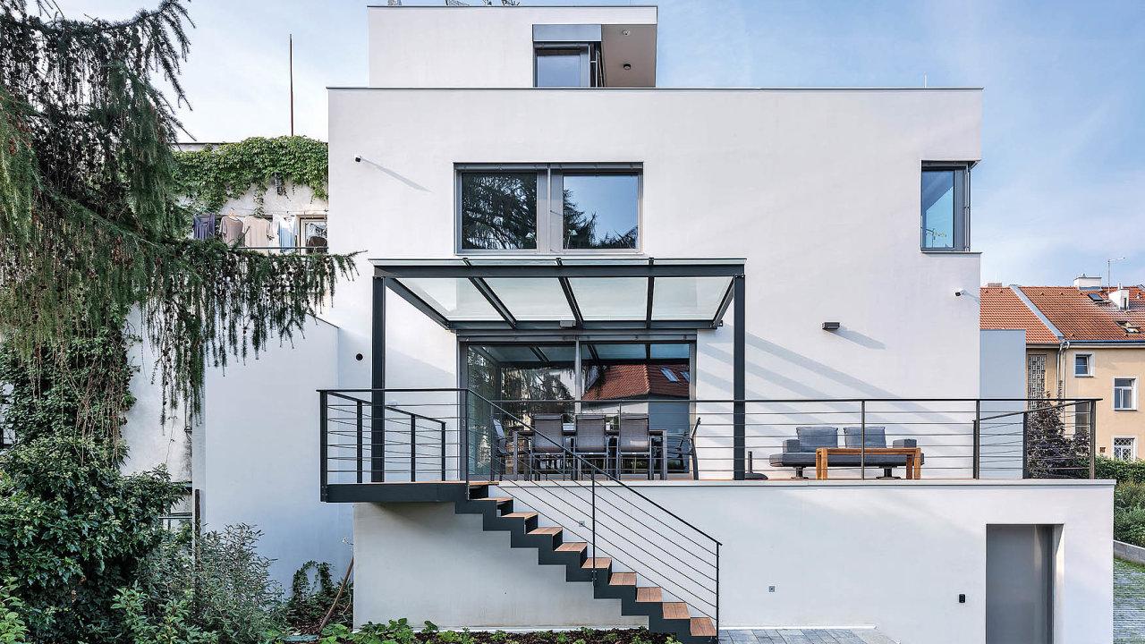 Při pohledu ze zahrady je dobře patrné, jak stupňovitá hmota domu graduje: vrcholí dětským ateliérem. Zterasy se sestupuje nazahradu, doníž je začleněn bazén.