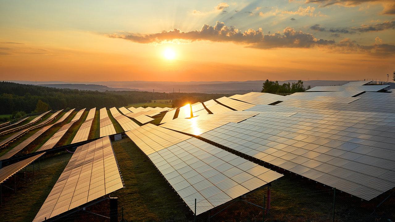 Fotovoltaické panely solární elektrárny v krajině při západu slunce.