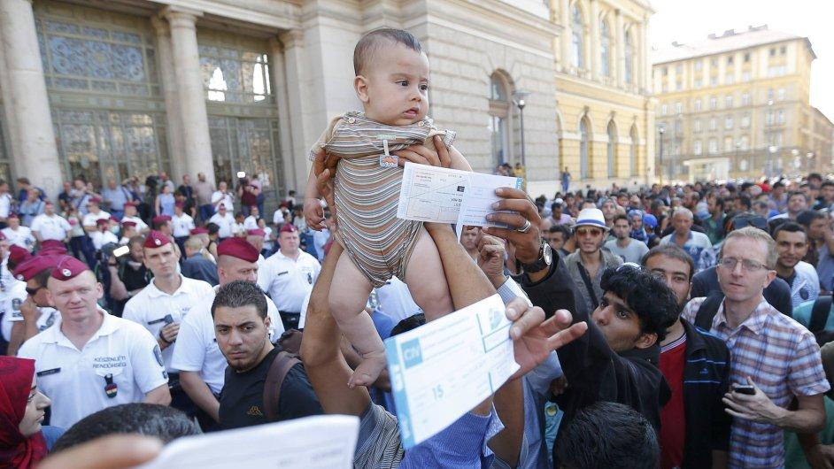 Migranti zvedají své děti a koupené lístky na protest před zavřeným nádražím Budapešť Keleti.