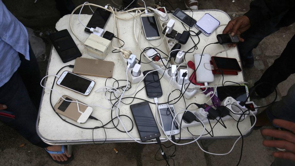 Uprchlíci si nabíjí telefony na vlakové stanici Gevgelija.