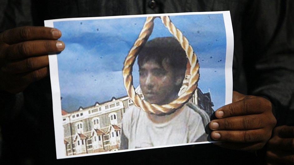 Muž drží fotografii popraveného Amira Kasaba