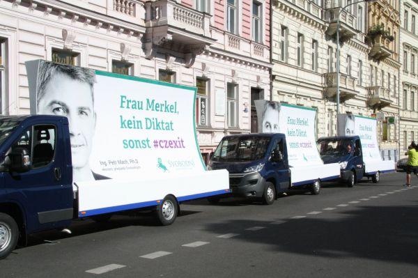 Auta s billboardy, protest Strany svobodných, návštěva Angely Merkelové
