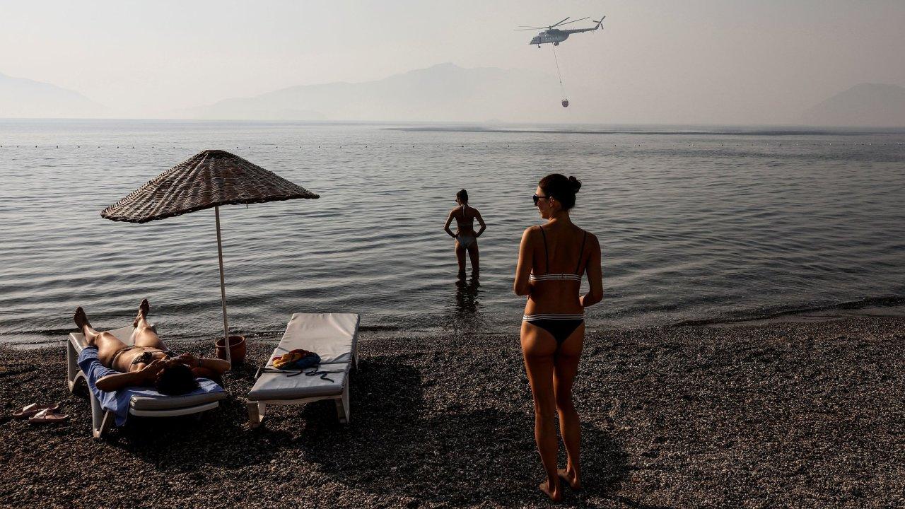 Turisté na pobřeží Egejského moře pozorují vrtulník, který nabírá vodu k hašení rozsáhlých požárů.