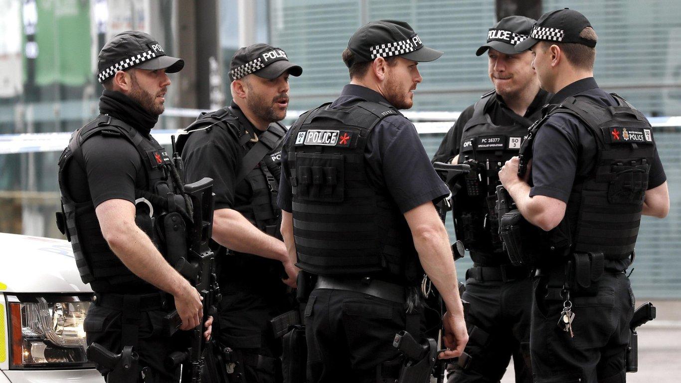 Ozbrojení policisté hlídají železniční stanici Victoria Station.