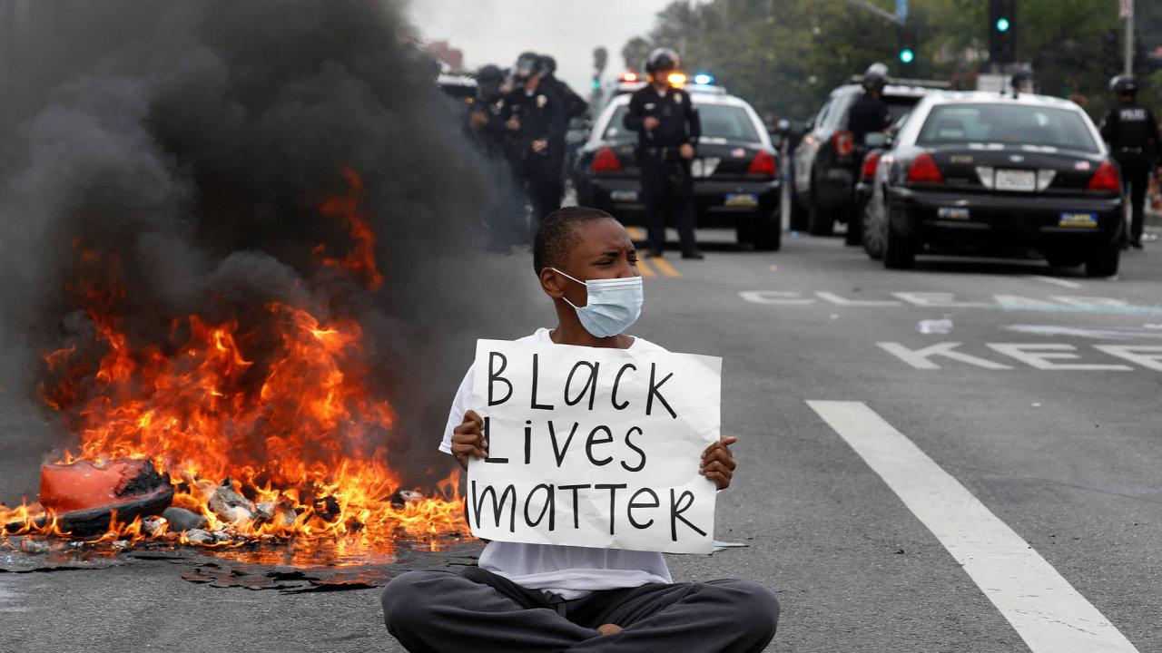 """Běhemprotestů vMinneapolisu drží demonstrant transparent sheslem """"Black Lives Matter"""" (Načernošských životech záleží)."""