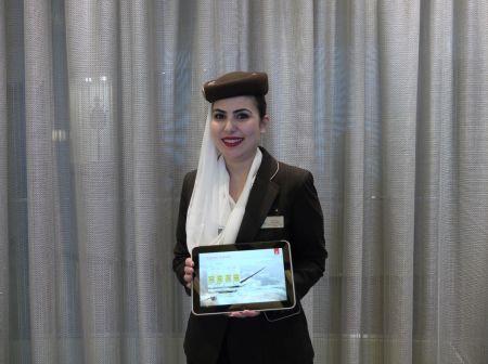 Členka palubních posádek Emirates ukazuje interní aplikaci aerolinek