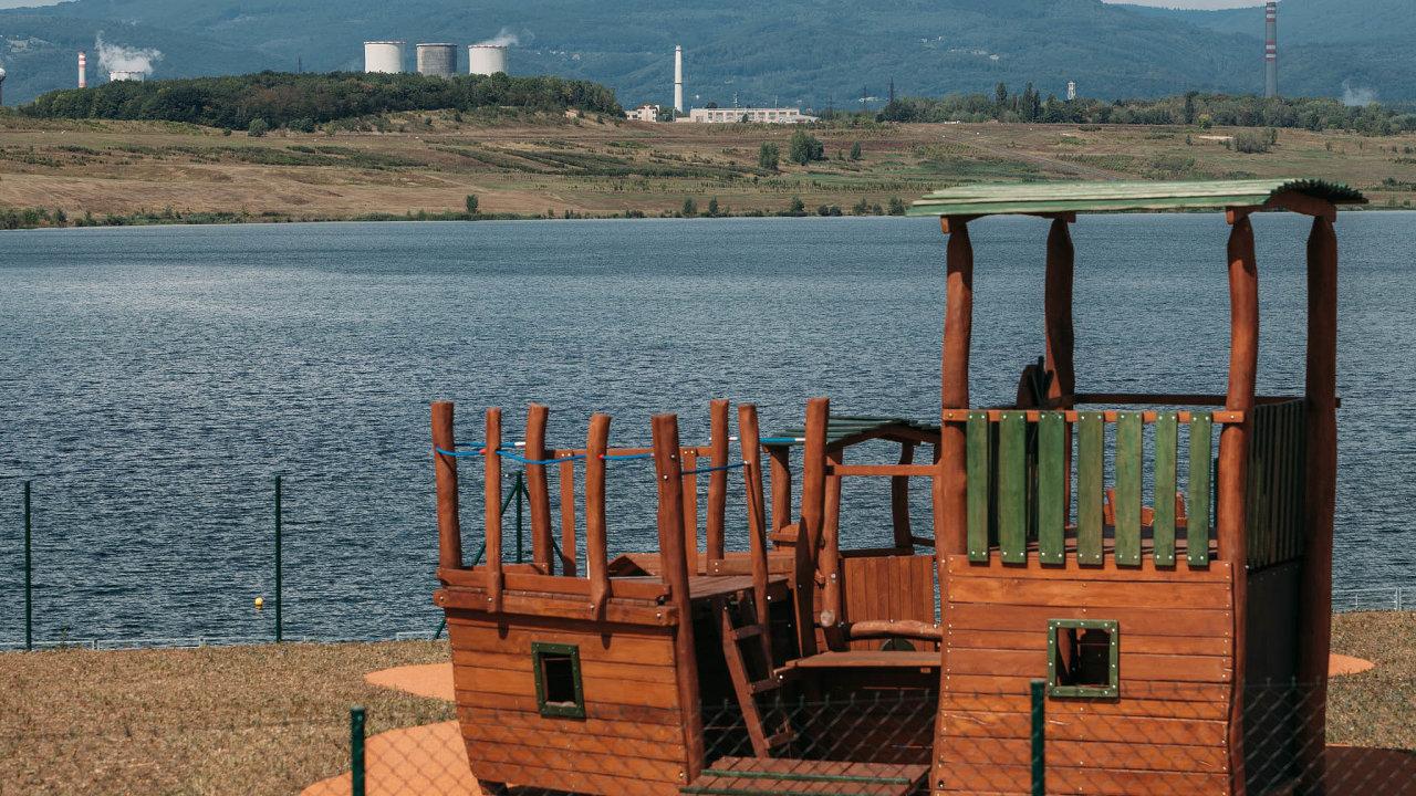 Jezero uMostu. Vodní plochu zjedné strany ohraničuje chemička Unipetrol azdruhé paneláky. Pod hladinou jezera leželo před padesáti lety nádherné středověké město.