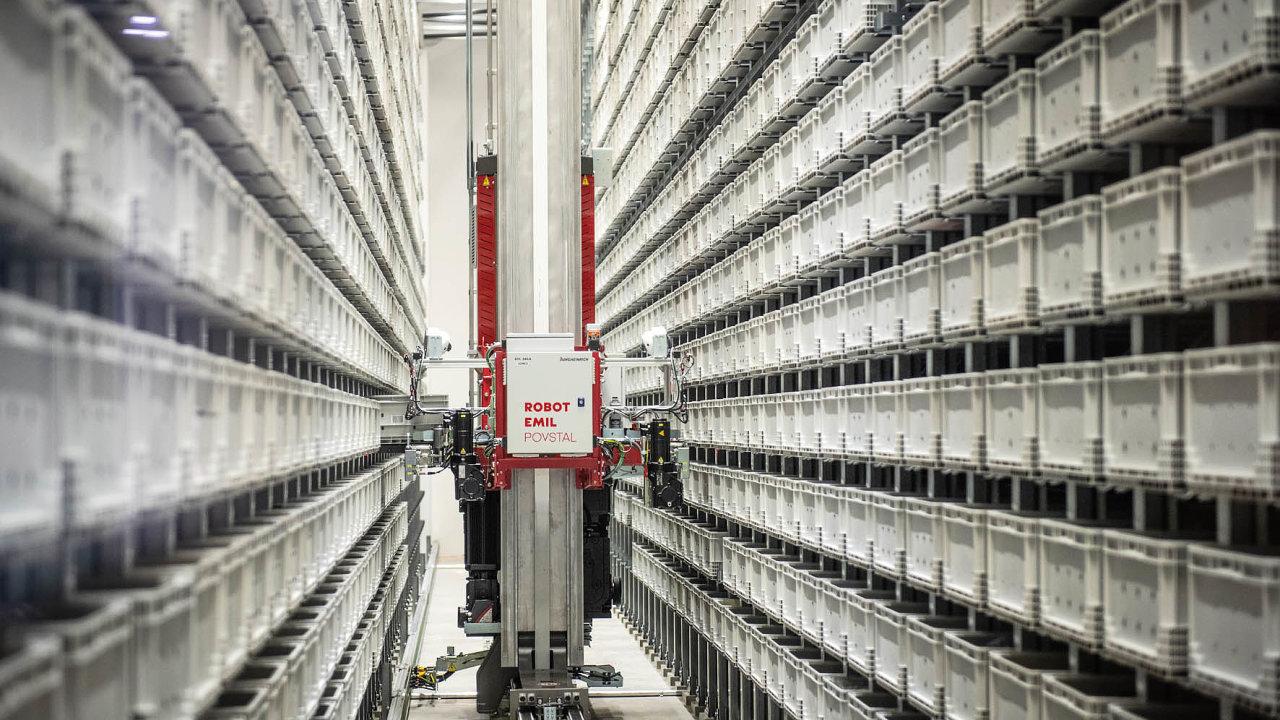 Robot se pohybuje uličkou mezi regály a vybírá z nich krabice s díly.