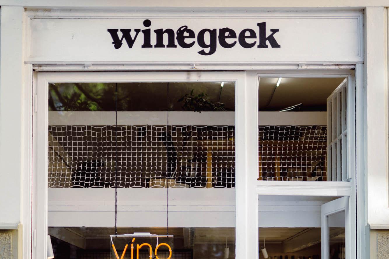 """Červený neon hlásající Víno teď nově osvětluje takzvaný """"Heřmaňák"""". Ochutnávkové six-packy nebo jednotlivé lahve výběrových naturálních vín si nechte zadarmo doručit až domů."""