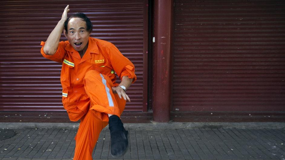Pouliční čistič předvádí svou dovednost bojového umění v přední části uzavřeného obchodu poblíž Pekingu na náměstí Nebeského klidu.