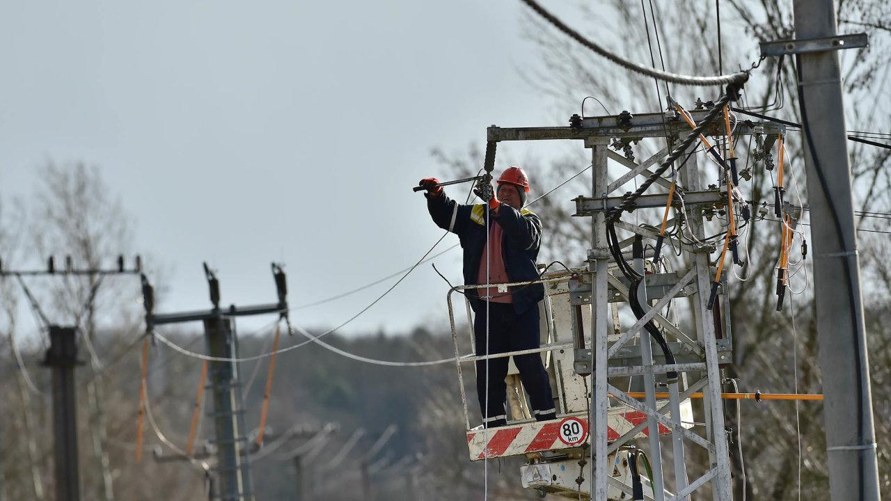 Pracovník energetické společnosti opravuje vedení zpřetrhané kvůli silnému větru.